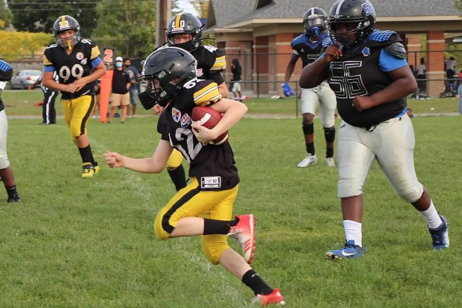 Augustus Guoin running the ball in for a touchdown during an Plymouth-Canton Steelers game.