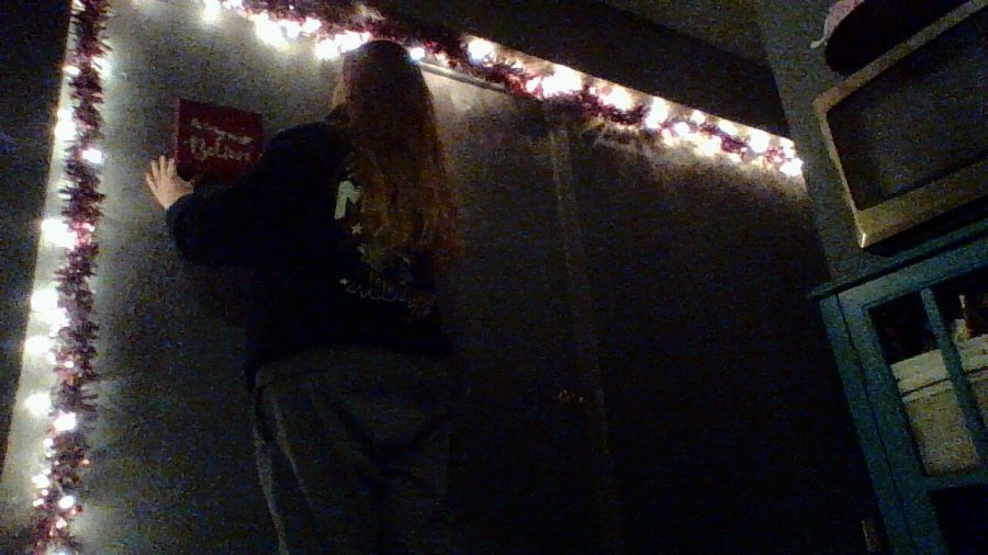 My mom putting up our Christmas decorations in our hallway.